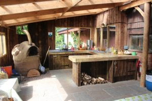 View of outdoor kitchen and cob oven